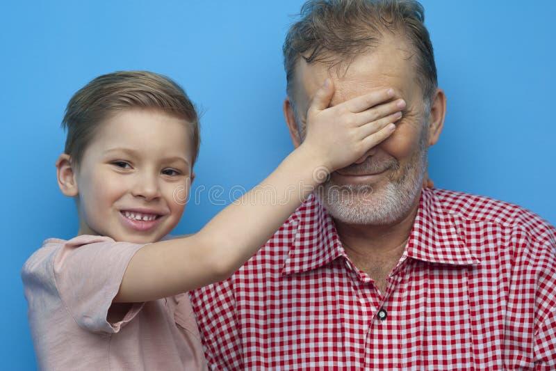 Il ragazzino positivo chiude gli occhi a suo nonno fotografia stock libera da diritti