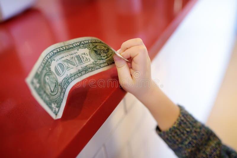 Il ragazzino ripaga la nota di valuta Bambini e concetto dei soldi fotografie stock