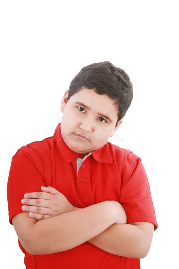 Il ragazzino serio con le mani ha piegato la condizione immagine stock