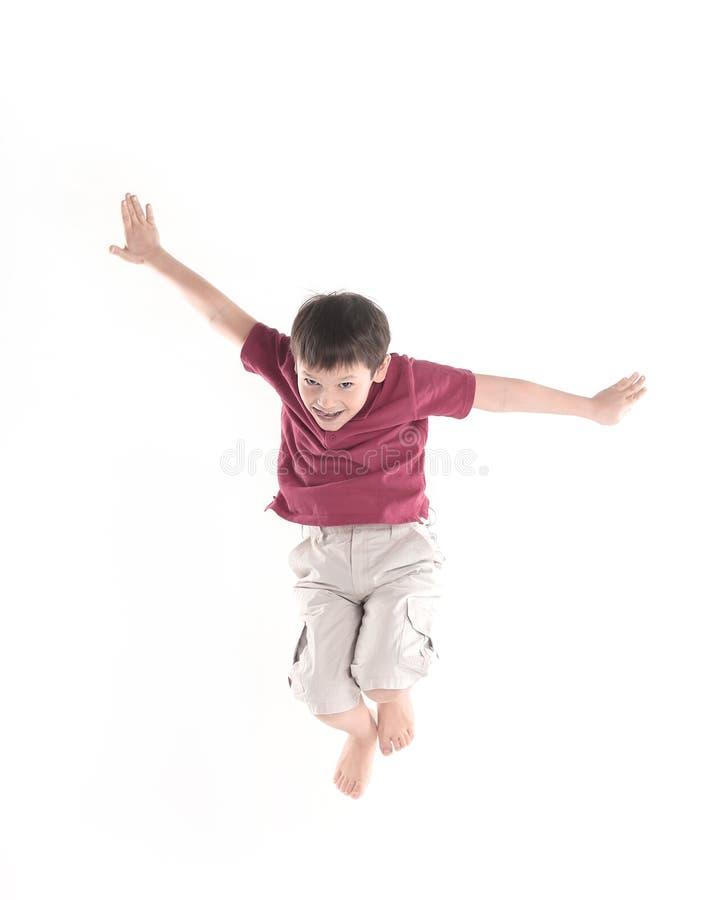 Il ragazzino si esercita di salto Isolato su bianco immagine stock libera da diritti