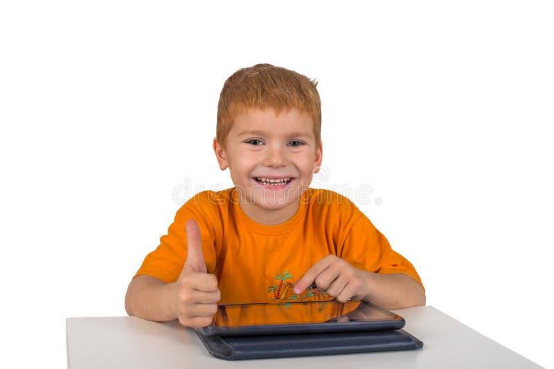 Il ragazzino si siede con il cuscinetto e mostra il gesto fotografia stock libera da diritti