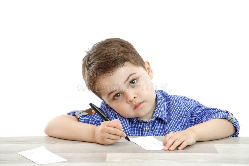 Il ragazzino si siede e disegna scrive su un fondo isolato fotografia stock libera da diritti
