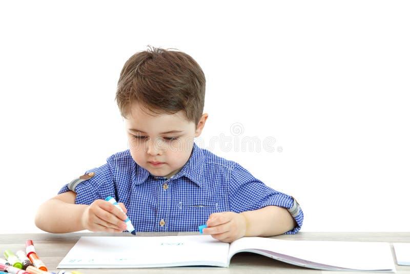 Il ragazzino si siede e disegna scrive su un fondo isolato immagine stock
