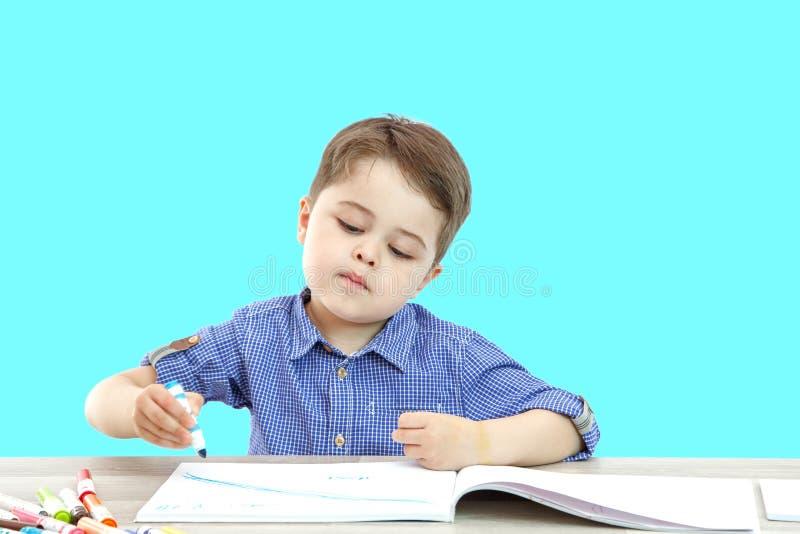 Il ragazzino si siede e disegna scrive su un fondo isolato fotografia stock