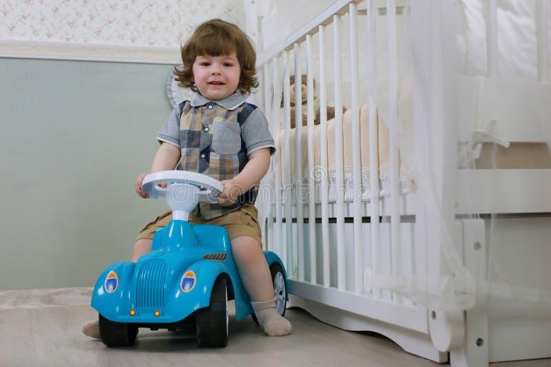 Il ragazzino si siede su un'automobile del giocattolo fotografia stock