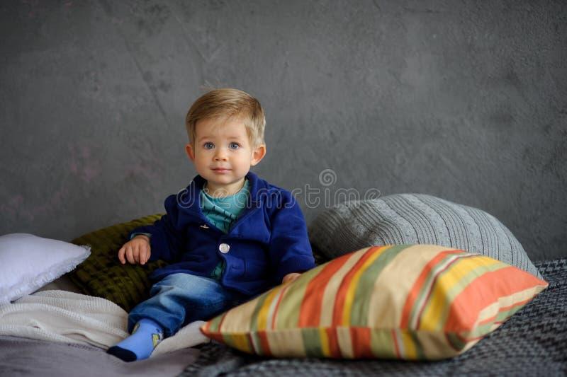 Il ragazzino si siede su un letto fotografie stock