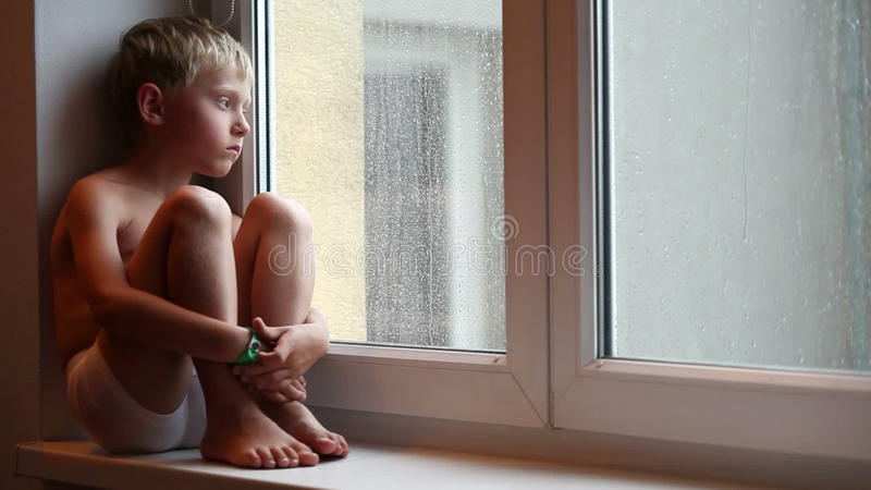 Il ragazzino solo aspetta i suoi genitori per venire a casa sedendosi sul davanzale archivi video