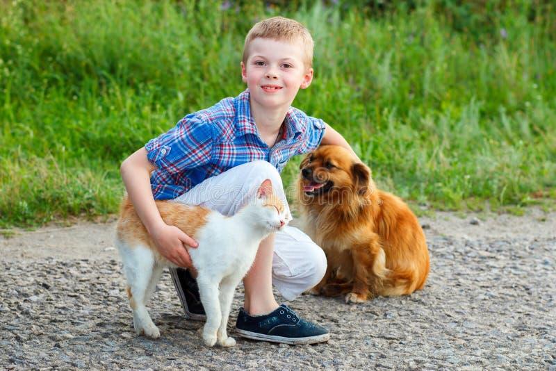 Il ragazzino sorridente con un gatto e un cane che si siedono sulla strada, il tipo che segna un cane, un gatto sfrega contro la  immagine stock