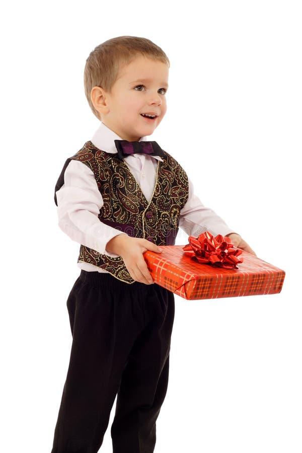 Il ragazzino sorridente dà un contenitore di regalo rosso immagine stock