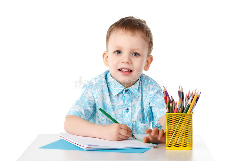 Il ragazzino sorridente disegna con i pastelli fotografie stock libere da diritti