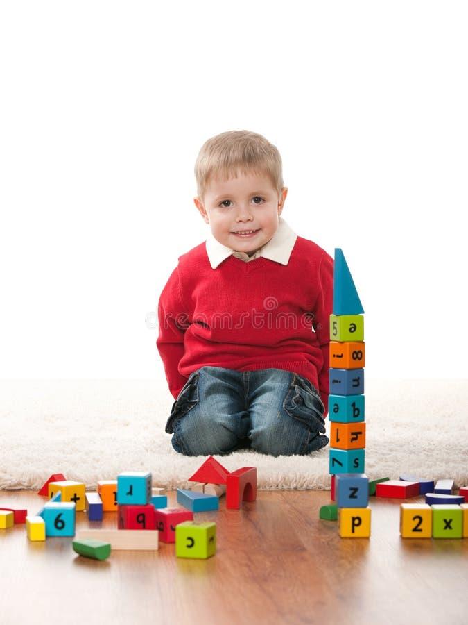 Il ragazzino sta giocando con l'alfabeto fotografia stock libera da diritti