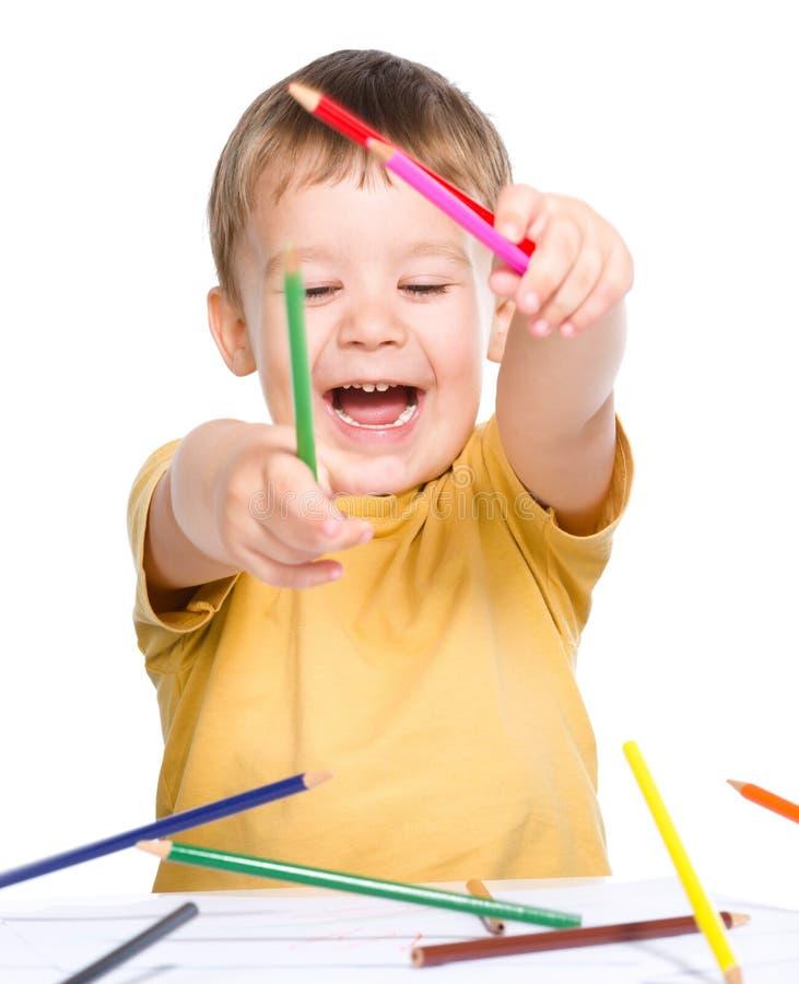Il ragazzino sta giocando con le matite di colore immagini stock