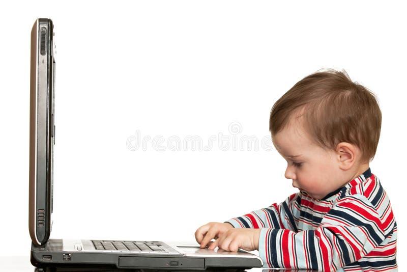 Il ragazzino sta lavorando con un computer portatile fotografia stock libera da diritti
