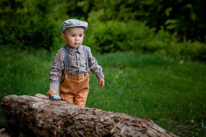 Il ragazzino sta mangiando il dolce, sull'automobile rossa del fondo, palloni nel parco Compleanno del bambino fotografie stock