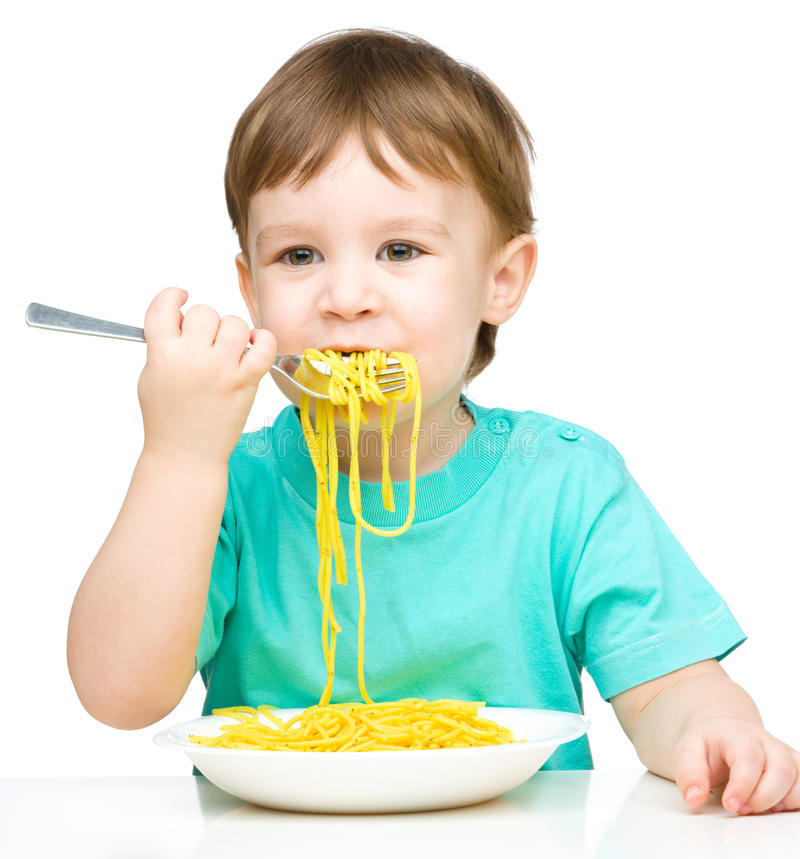 Il ragazzino sta mangiando gli spaghetti fotografia stock libera da diritti