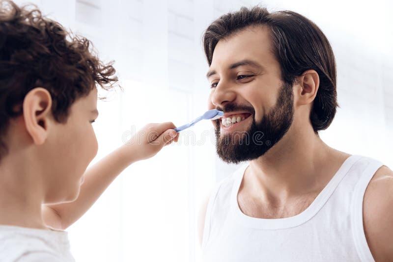 Il ragazzino sta pulendo i denti dell'uomo barbuto con lo spazzolino da denti immagine stock libera da diritti