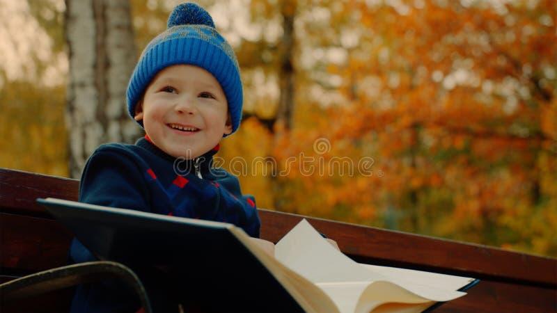 Il ragazzino sta sorridendo con il grande album della famiglia nel parco di autunno fotografie stock libere da diritti