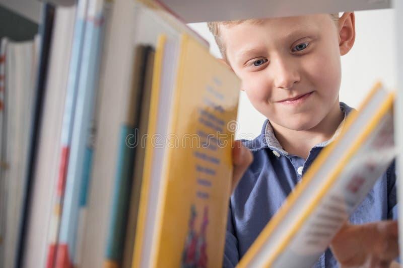 Il ragazzino sveglio sceglie un libro sullo scaffale per libri fotografie stock