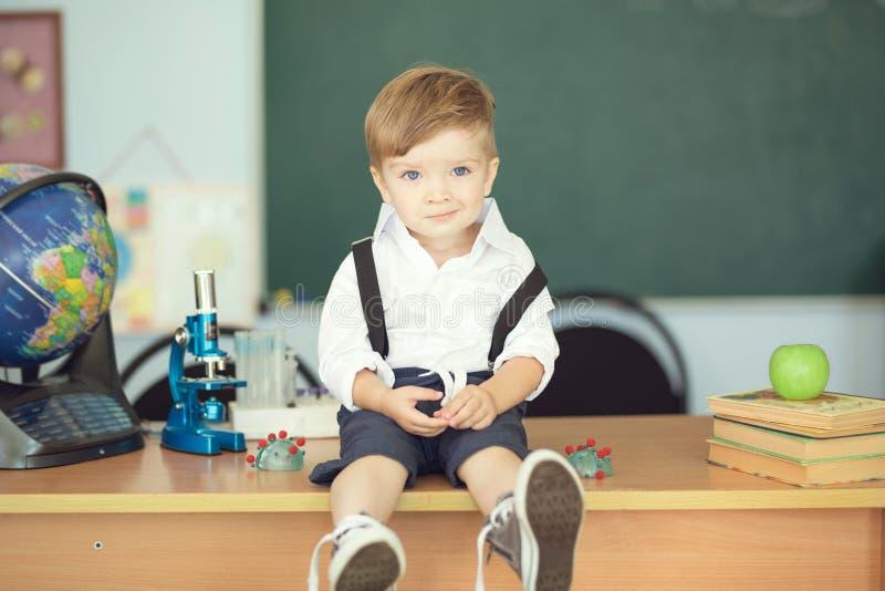 Il ragazzino sveglio si siede sullo scrittorio e sul sorridere nell'aula sul fondo della lavagna immagini stock libere da diritti