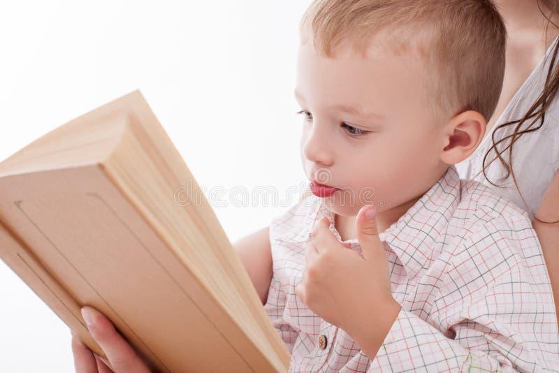 Il ragazzino sveglio sta imparando leggere immagini stock