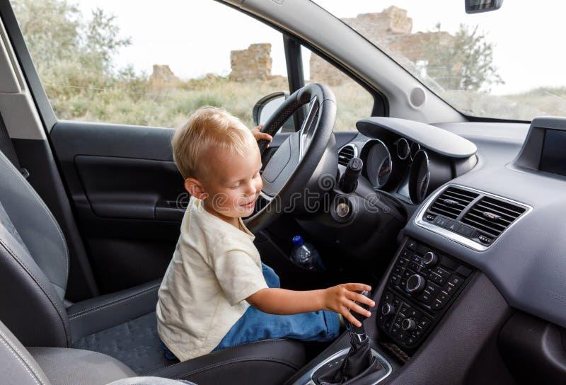 Il ragazzino sveglio sta sedendosi alla ruota di un'automobile e sta provando sul ruolo dell'autista immagini stock libere da diritti
