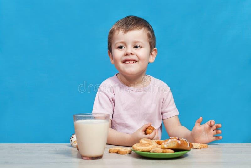 Il ragazzino sveglio sta sorridendo, latte alimentare e sta mangiando i biscotti immagini stock libere da diritti