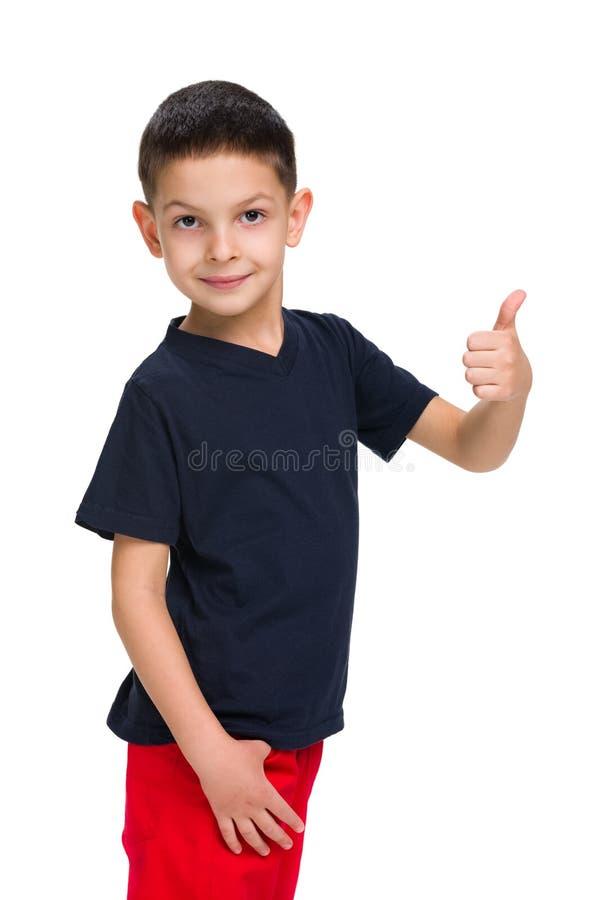 Il ragazzino sveglio tiene il suo pollice su fotografie stock libere da diritti