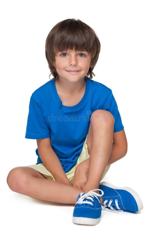 Il ragazzino sveglio in una camicia blu si siede fotografia stock libera da diritti