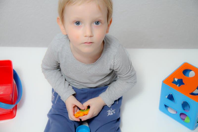 Il ragazzino tre anni si siede sulla tavola ed i giochi con plasticine e giocattoli, cubi e dadi di legno e di plastica immagine stock libera da diritti