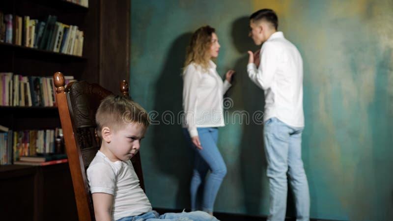 Il ragazzino triste ? genitori di divorzio d'ascolto combatte immagine stock