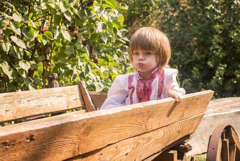 Il ragazzino in un bianco ha ricamato la camicia divertendosi in un vecchio carretto immagini stock libere da diritti