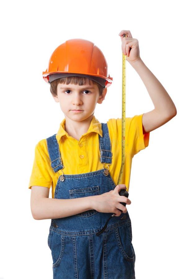 Il ragazzino in un casco gioca nel costruttore fotografia stock