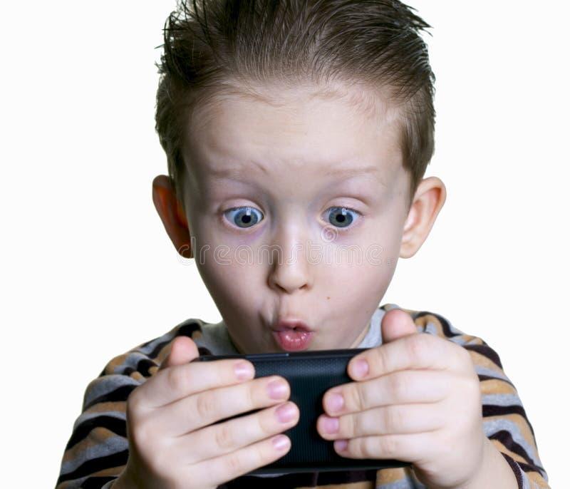Il ragazzo è stato sorpreso osservare nel telefono fotografia stock libera da diritti