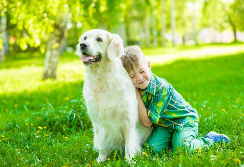 Il ragazzo abbraccia un cane di golden retriever sull'erba verde fotografia stock libera da diritti