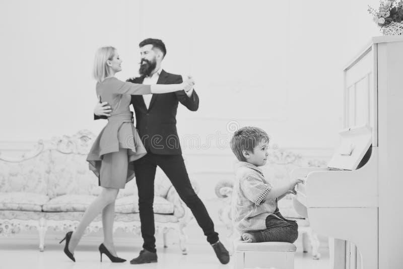 Il ragazzo adorabile prova a giocare lo strumento musicale del piano, mentre ballare dei genitori Concetto di istruzione del musi fotografia stock