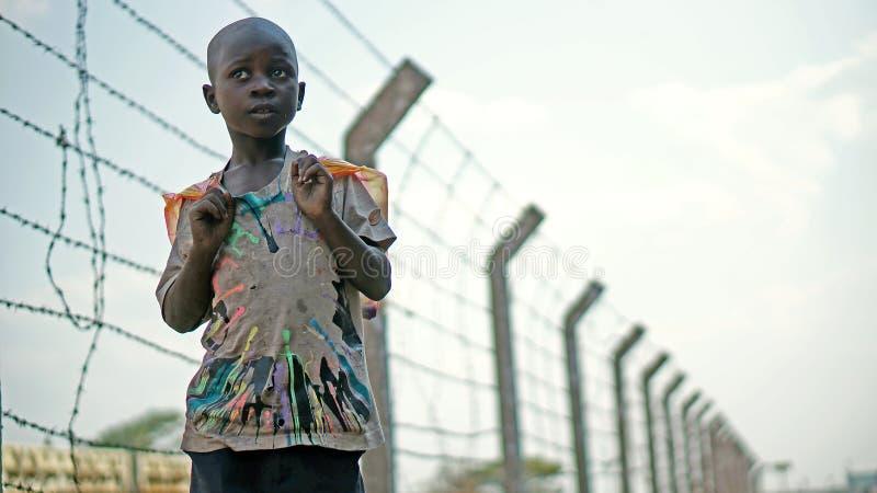 Il ragazzo africano sta su un fondo di filo spinato lungo la ferrovia fotografie stock