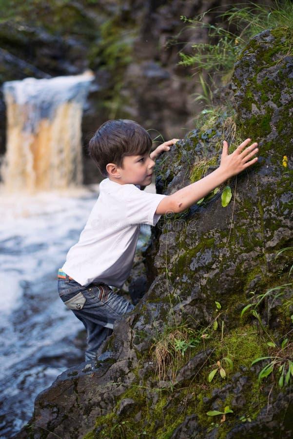 Il ragazzo alla cascata immagine stock