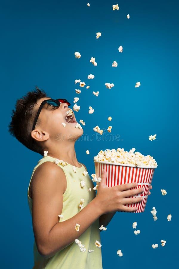 Il ragazzo allegro con un secchio di popcorn, molto popcorn cade da sopra, il ragazzo prende lui, il divertimento e lo spettacolo fotografia stock libera da diritti