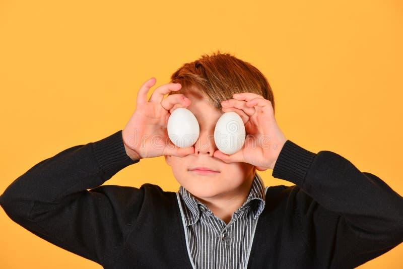 Il ragazzo allegro e allegro tiene le uova di Pasqua sui suoi occhi immagine stock