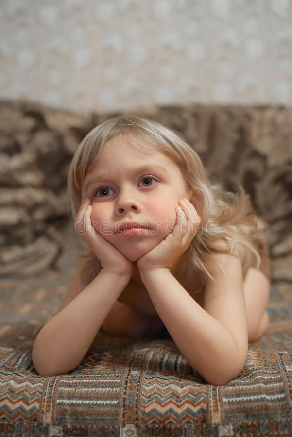 Il ragazzo 4 anni a casa sta trovandosi sullo strato e sulla TV di sorveglianza Ritratto di un ragazzo biondo immagini stock