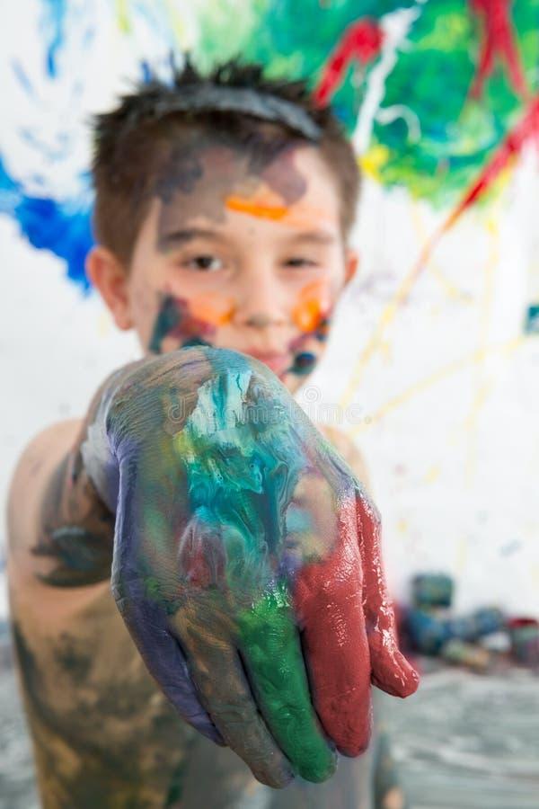 Il ragazzo artistico che dà la sua pittura ha riguardato la mano fotografia stock