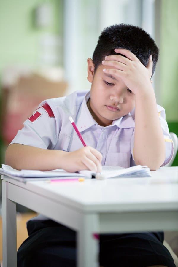 Il ragazzo asiatico è annoiato facendo il suo compito immagini stock