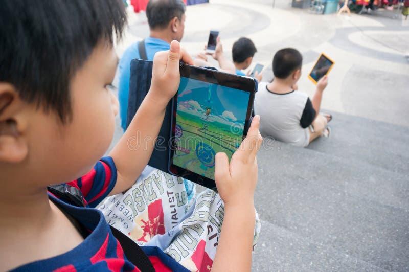 Il ragazzo asiatico che gioca un Pokemon accende cuscinetto i mini2 del gioco immagine stock