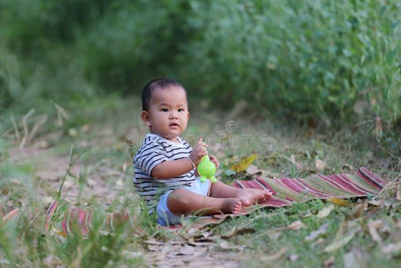 Il ragazzo asiatico del bambino si siede sulla stuoia tailandese nel giardino immagine stock libera da diritti