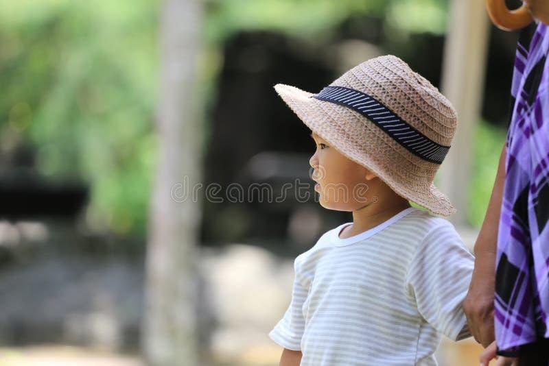 Il ragazzo asiatico ha interessi mentre nello zoo fotografia stock libera da diritti
