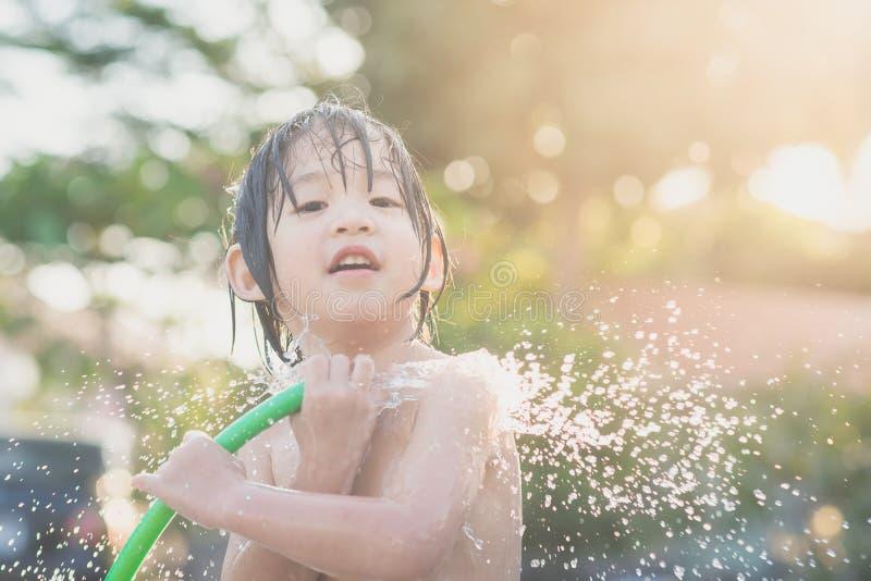 Il ragazzo asiatico sveglio si diverte il gioco in acqua da un tubo flessibile fotografia stock