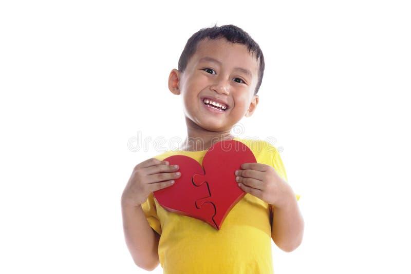 Il ragazzo asiatico sveglio tiene un cuore immagini stock
