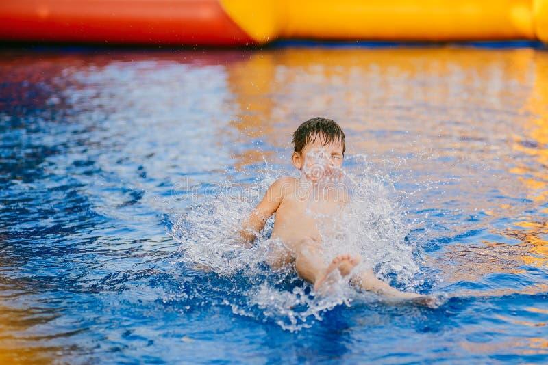 Il ragazzo bagna nello stagno del ` s dei bambini ragazzo che gioca nello stagno gonfiabile immagine stock libera da diritti