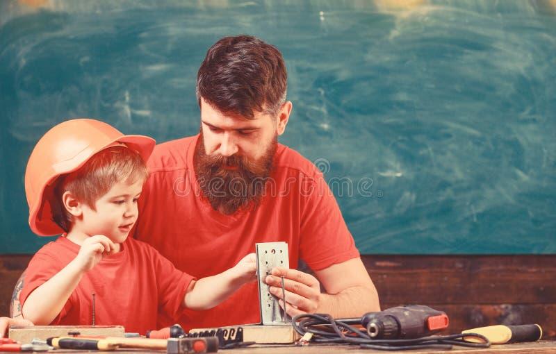 Il ragazzo, bambino occupato in casco protettivo fa a mano, riparando con il papà Generi con la barba che insegna al piccolo figl fotografia stock