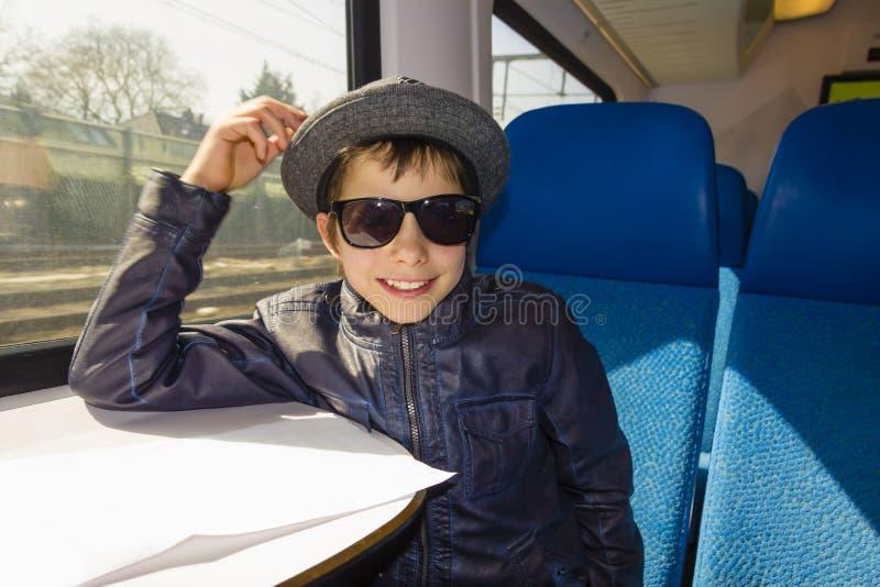 Il ragazzo bello con gli occhiali da sole guida su una lettura del treno dalla carta fotografia stock libera da diritti